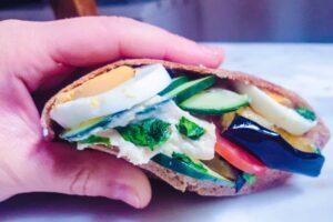 Sándwich Vegano de pan pita con vegetales salteados Hummus verde y ensalada fresca